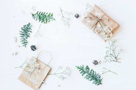 Weihnachtskomposition. Weihnachtsgeschenk, Tannenzapfen, Thuja Zweige und Gypsophila Blumen. Draufsicht, flache Lage