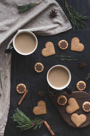 Christmas composition. Cup of coffee, christmas cookies, pine branch, cinnamon sticks, anise star. Flat lay, top view