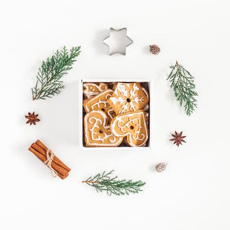 クリスマスの組成物。クリスマスのジンジャーブレッド クッキーと白い背景の上の松の枝。フラットを置く、広場平面図 写真素材