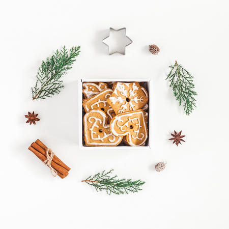 Christmas composition. Christmas gingerbread cookies and pine branches on white background. Flat lay, top view, square