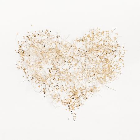 Composizione di Natale. Simbolo di cuore fatta di decorazioni dorate di natale su sfondo bianco. Vista dall'alto, piano piano, quadrato