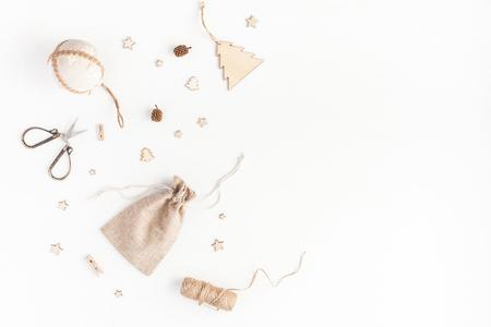 Weihnachtskomposition. Weihnachtsgeschenke, Kiefernkegel, hölzerne Dekorationen auf weißem Hintergrund. Flache Lage, Draufsicht, Kopie, Raum