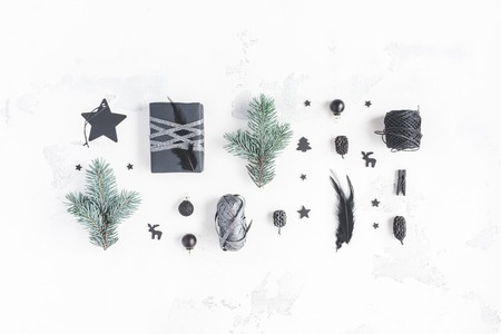 Composition de Noël. Cadeaux de Noël, pommes de pin, branches de sapin, décorations noires sur fond blanc. Plat poser, vue de dessus