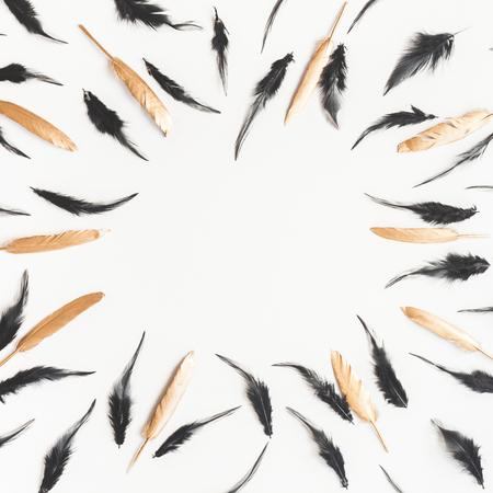 Frame gemaakt van gouden en zwarte vogelveren. Plat leggen, bovenaanzicht, kopie ruimte, vierkant Stockfoto