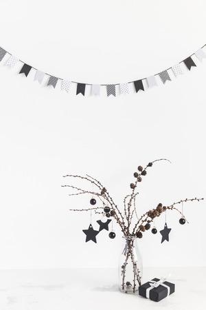 Weihnachts-Komposition. Lärchenzweige, Geschenk und schwarze Dekorationen auf weißem Hintergrund. Weihnachten, Winter, Konzept des neuen Jahres. Vorderansicht