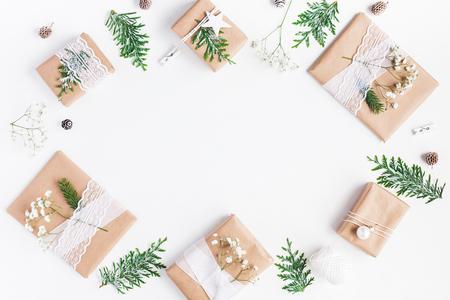 Рождественская композиция. Рамка из рождественских подарков, сосновые шишки, цветы гипсофилы, ветки thuja на белом фоне. Квартира, вид сверху, место для копирования