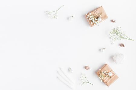 Composição do Natal. Quadro feito de presentes de natal, cones de pinho, flores de gypsophila no fundo branco. Leito plano, vista superior, espaço de cópia Foto de archivo