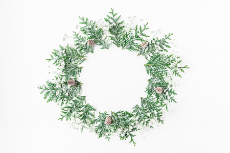 クリスマスの組成物。Thuja 枝、カスミソウの花、白い背景の上の松ぼっくりのリース。クリスマス、冬、新年の概念。コピー スペース フラット横た