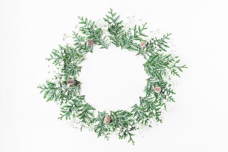 Weihnachts-Komposition. Der Kranz, der von den Thujaniederlassungen gemacht wird, Gypsophilablumen, Kiefernkegel auf weißem Hintergrund. Weihnachten, Winter, Konzept des neuen Jahres. Flachlage, Draufsicht, Kopienraum