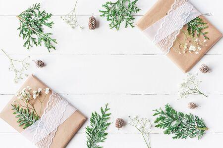 Kerst samenstelling. Kader van Kerstmisgiften, denneappels, gypsophila bloemen, thuja takken op witte houten achtergrond wordt gemaakt die. Plat leggen, bovenaanzicht, kopie ruimte Stockfoto