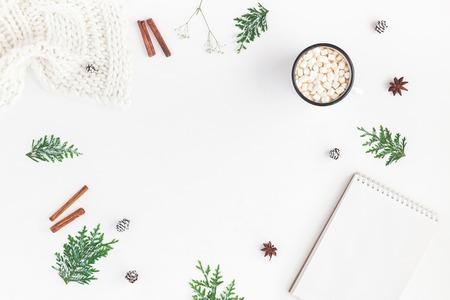 Composizione di Natale Cioccolata calda, coperta, taccuino, rami di thuya, bastoncini di cannella su sfondo bianco. Vista piana, vista dall'alto, copia spazio