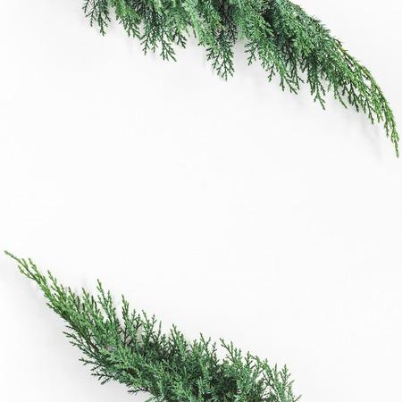 Kerstmissamenstelling van pijnboomtakken wordt gemaakt op witte achtergrond die. Kerstmis, winter, nieuw jaar concept. Plat leggen, bovenaanzicht, kopie ruimte Stockfoto