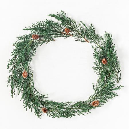 クリスマスの組成物。ヒノキ枝、白い背景の上の松ぼっくりのクリスマス リース。フラットを置く、平面図、正方形領域をコピー