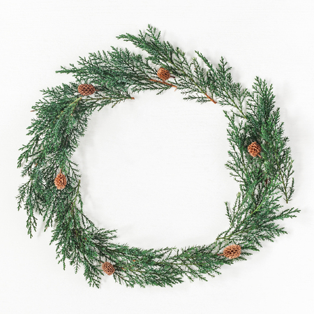 Christmas composition. Christmas wreath made of cypress branches, pine cones on white background. Flat lay, top view, copy space, square Stock Photo
