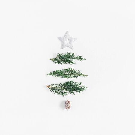 Kerstboom gemaakt van cypress takken en zilveren decoraties. Kerstmis, winter, nieuw jaar concept. Plat leggen, bovenaanzicht, vierkant