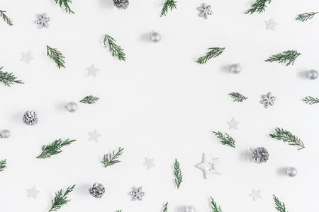クリスマスの組成物。フレームは、クリスマスの装飾品をシルバーし、松の枝の白い背景の上に作られて。コピー スペース フラット横たわっていた