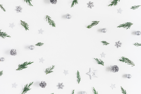 Kerst samenstelling. Kader dat van Kerstmis zilveren decoratie en pijnboomtakken wordt gemaakt op witte achtergrond. Plat leggen, bovenaanzicht, kopie ruimte