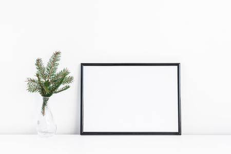 クリスマスの組成物。ブラック フレームとクリスマス トレの枝は白い背景の上。正面、モックアップ、スペースをコピー 写真素材