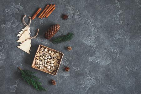 Weihnachts-Komposition. Zypresse verzweigt sich und hölzerne Weihnachtsdekorationen auf dunklem Hintergrund. Flachlage, Draufsicht, Kopienraum