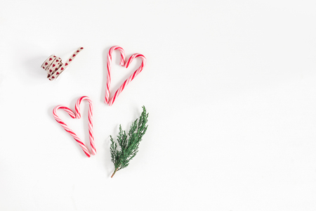 Christmas composition. Christmas candy canes and fir branches on white background. Flat lay, top view, copy space
