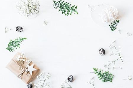 聖誕節組成。聖誕節禮物,松果,崖柏分支和滿天星鮮花。頂視圖,平躺