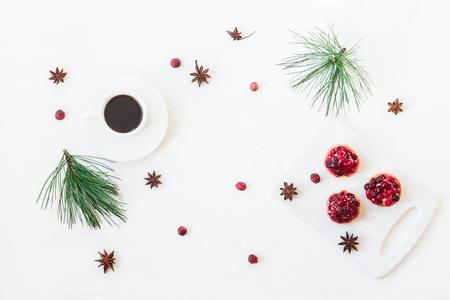 Kerst samenstelling. Kopje koffie, kerst dessert, anijs ster, pijnboomtakken. Plat leggen, bovenaanzicht Stockfoto