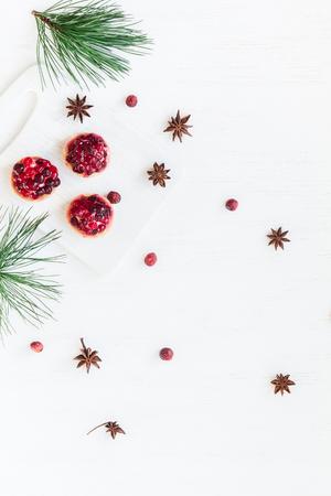 Рождественская композиция. Рождественский десерт из клюквы, анисовая звезда. сосны. Плоский, вид сверху