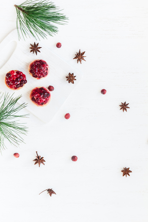 Christmas composition. Christmas dessert of cranberries, anise star. pine branches. Flat lay, top view