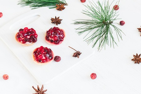 Christmas composition. Christmas dessert of cranberries, anise star. pine branches.
