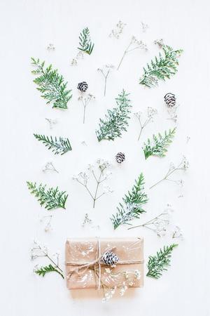 Рождественская композиция. Рождественский подарок, сосновые шишки, ветки туи и цветы гипсофилы. Вид сверху, квартира