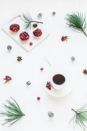 Kerst samenstelling. Kopje koffie, kerst dessert, anijs ster, pijnboomtakken. Bovenaanzicht