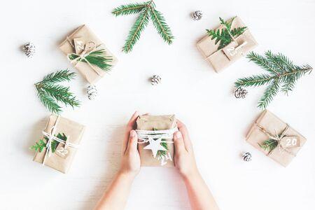 聖誕節日曆。聖誕禮物,冷杉的枝條,松果。孩子的手。平躺,頂視圖