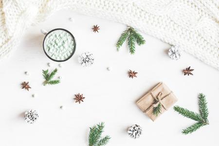Weihnachts-Komposition. Heiße Schokolade, Weihnachtsgeschenk, gestrickte Decke, Tannenzapfen, Tannenzweigen. Flache Lage, Draufsicht