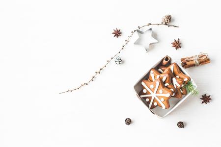 Kerst samenstelling. Gift, lariks takken, kaneelstokjes, anijs ster, kerstkoekjes. Plat leggen, bovenaanzicht Stockfoto