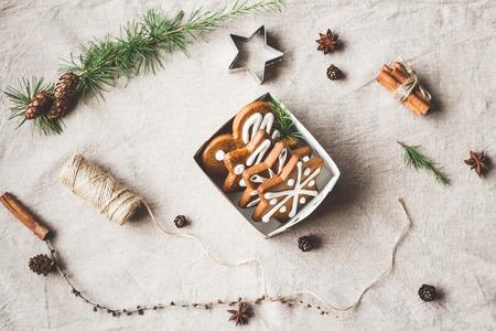 Composizione di Natale. Regalo, rami di larice, bastoncini di cannella, stella di anice, biscotti di Natale. Vista dall'alto, pianeggiante Archivio Fotografico