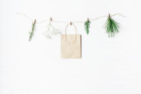 Бумажный мешок, ветки хвойных деревьев, цветы гипсофилы. Зимняя концепция. Плоский, вид сверху