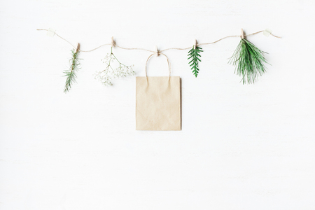 Paper bag, conifers branches, gypsophila flowers. Winter concept. Flat lay, top view Foto de archivo