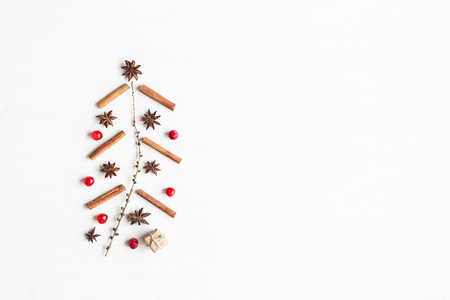 Christmas tree made of cinnamon sticks, anise star, larch branches, cranberries. Christmas concept. Flat lay, top view