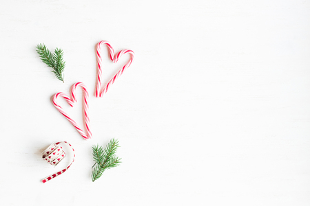 Christmas composition. Christmas candy canes and fir branches. Flat lay, top view