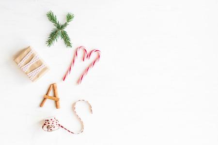 Composizione di Natale Bastoncini di zucchero natalizio, regali, bastoncini di cannella e rami di abete. Vista piana, vista dall'alto