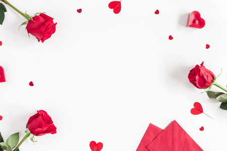 Valentine's Day. Frame made of rose flowers, gifts, candles, confetti on white background. Valentines day background. Flat lay, top view, copy space