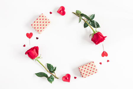 Valentine's Day. Round frame made of rose flowers, gifts, candles, confetti on white background. Valentines day background. Flat lay, top view, copy space