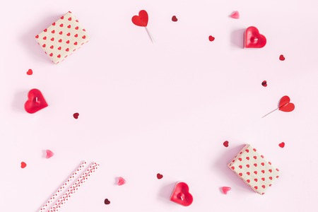 Valentines Day. Frame made of gifts, candles, confetti on pink background. Valentines day background. Flat lay, top view, copy space