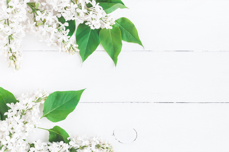 Flowers composition. Frame made of white lilac flowers on white wooden background. Flat lay, top view, copy space Zdjęcie Seryjne