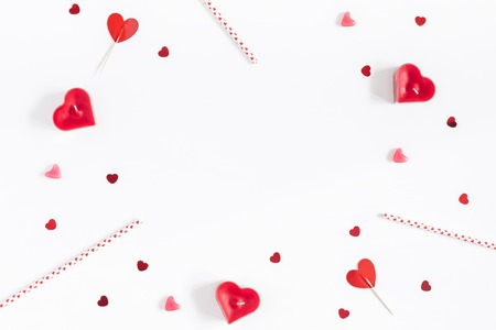 Valentine's Day. Frame made of candles, confetti on white background. Valentines day background. Flat lay, top view, copy space
