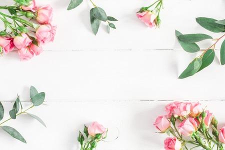 Composición de las flores. Capítulo hecho de ramas del eucalipto y de flores de la rosa del rosa en el fondo de madera blanco. Plano, vista desde arriba, copia espacio