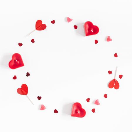 Valentijnsdag. Frame gemaakt van kaarsen, confetti op witte achtergrond. Valentijnsdag achtergrond. Plat lag, bovenaanzicht, kopie ruimte, vierkant Stockfoto
