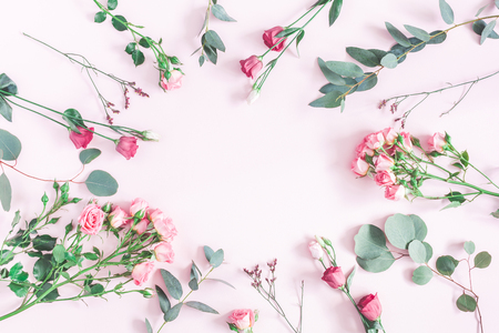 Flowers composition. Round frame made of various pink flowers and eucalyptus branches on pink background. Flat lay, top view, copy space
