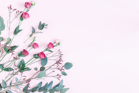 Flowers composition. Frame made of various pink flowers and eucalyptus branches on pink background. Flat lay, top view, copy space Archivio Fotografico