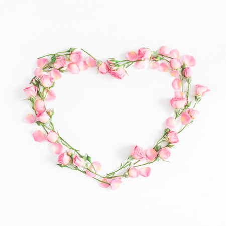 Flowers composition. Heart symbol made of pink rose flowers on white background. Flat lay, top view, copy space, square
